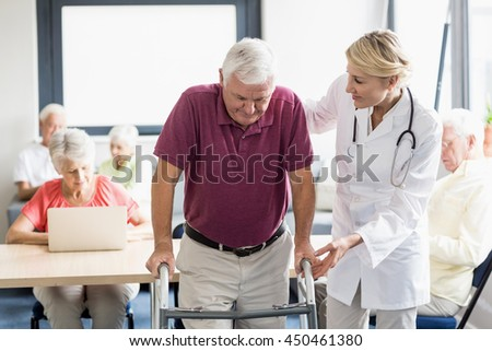 Nurse helping senior with walking aid in a retirement home
