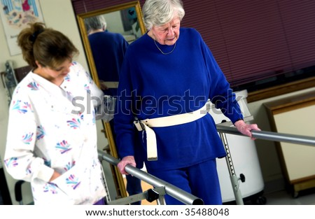 nurse helping senior woman with physical rehabilitation - stock photo