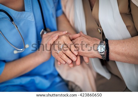 Nurse holding a hands to elderly woman - stock photo