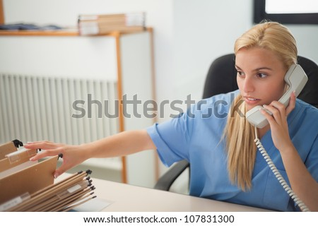 Nurse holding a phone while searching a folder in hospital reception - stock photo