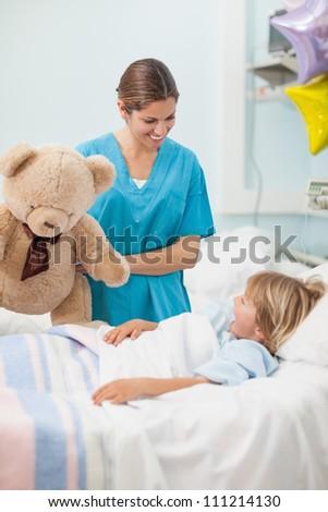 Nurse holding a teddy bear in hospital ward - stock photo