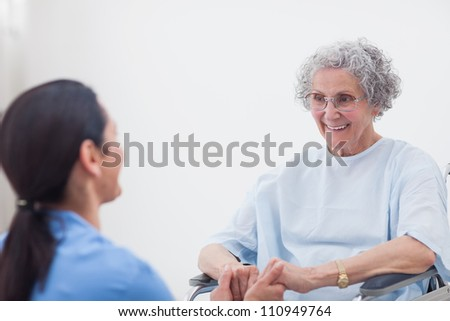 Nurse holding hands of a patient in hospital ward - stock photo