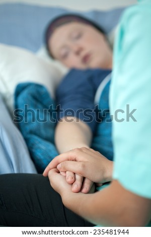 Nurse holding the sick female patient's hand in hospital - stock photo