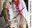 Nurse in a hospital asking a senior woman in wheelchair for signature - stock photo