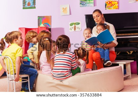 Nurse in kindergarten read book to the class - stock photo