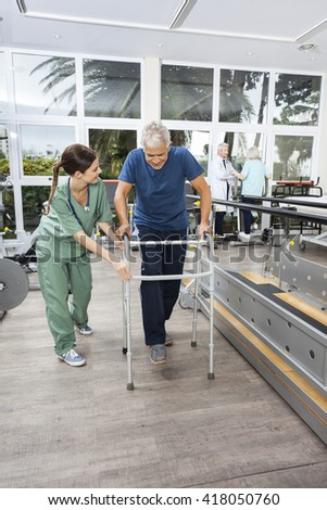 Nurse In Scrubs Assisting Man With Walker At Fitness Studio - stock photo