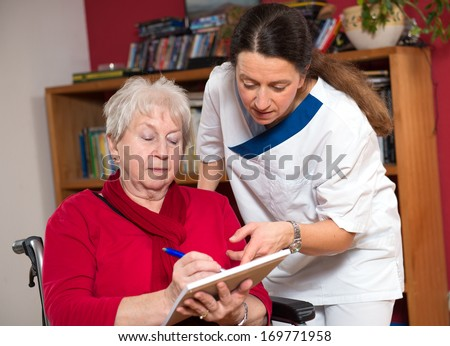 nurse is helping a old woman with a form - stock photo