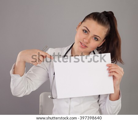 Nurse is with a paper at the table against of grey background