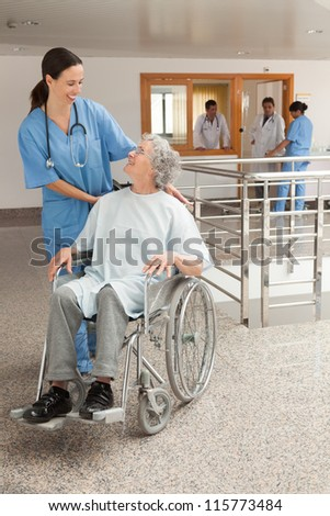 Nurse laughing with old women sitting in wheelchair in hospital corridor - stock photo