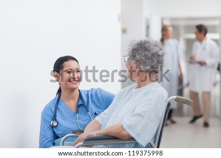 Nurse looking at a patient in a wheelchair in hospital ward - stock photo