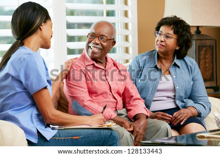 Nurse Making Notes During Home Visit With Senior Couple