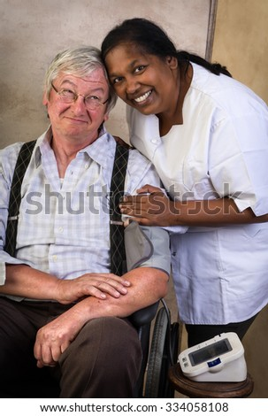Nurse measuring blood pressure of an elderly man in a wheelchair - stock photo