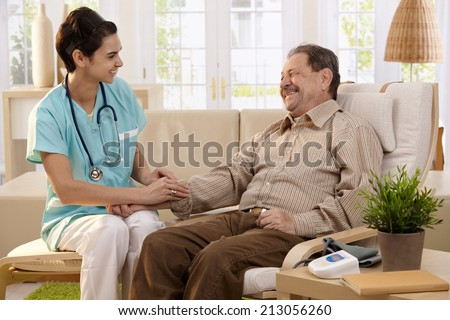 Nurse measuring blood pressure of senior man at home. Smiling to each other. - stock photo