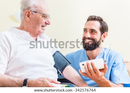 Nurse measuring blood pressure of senior patient - stock photo