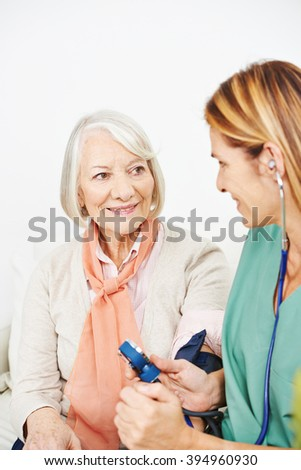 Nurse monitoring blood pressure for senior woman in nursing home - stock photo