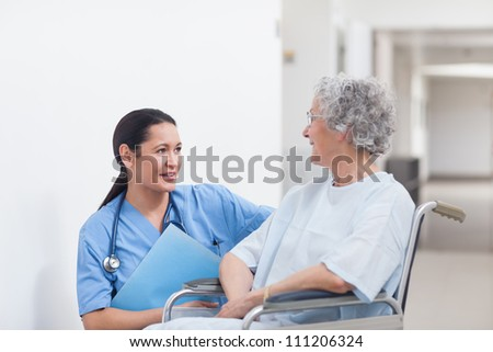 Nurse next to a patient in a wheelchair in hospital ward - stock photo