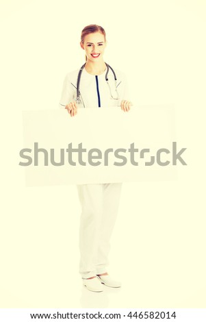 Nurse or doctor holding empty white board. - stock photo
