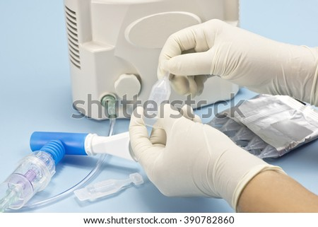 Nurse prepares albuterol sulfate vial for use in medication cup for inhalation therapy.  Albuterol is a common medication name. - stock photo