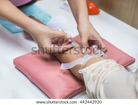 nurse pricking needle syringe to collect blood for test the health