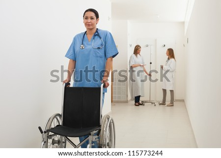 Nurse pushing empty wheelchair with doctor and patient talking in hospital corridor - stock photo