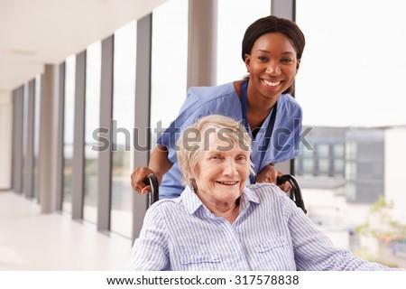 Nurse Pushing Senior Patient In Wheelchair Along Corridor - stock photo