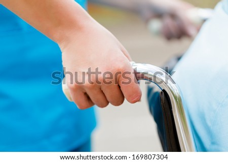 Nurse pushing wheelchair outdoors with patient. - stock photo