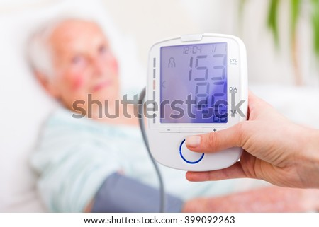 Nurse registering sick elderly patient's systolic and diastolic blood pressure in bed with the heart rate.