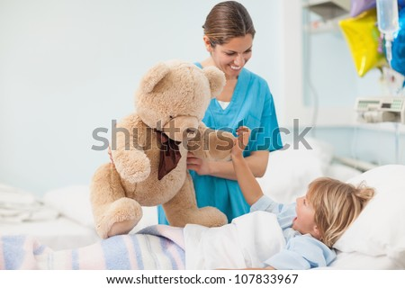 Nurse showing a teddy bear to a child in hospital ward