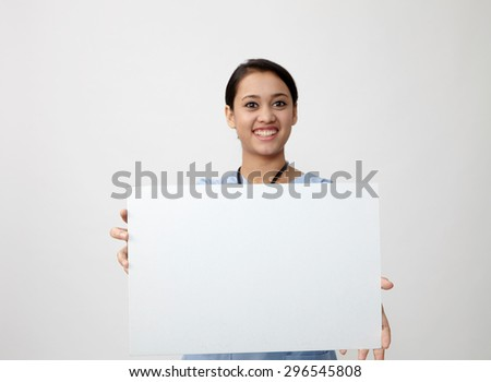 Nurse showing medical sign billboard standing, Young smiling woman nurse or doctor in scrubs showing empty blank sign board with copy space. Indian model isolated on white background - stock photo