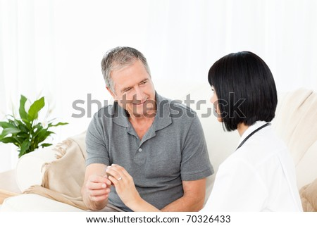 Nurse showing pills to her mature  patient