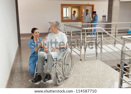 Nurse smiling and kneeling beside old women sitting in wheelchair - stock photo