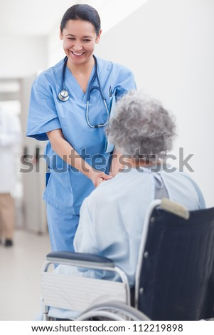 Nurse smiling while holding the hands of a patient in hospital ward - stock photo