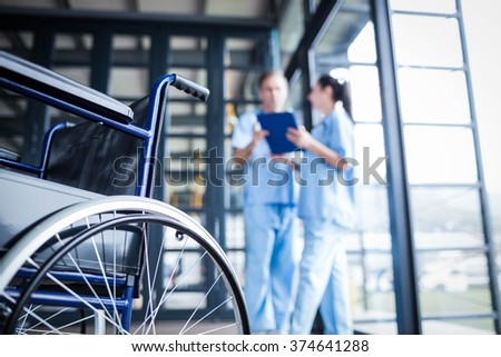 Nurse staff bringing a wheelchair at the hospital - stock photo
