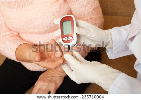 Nurse takes test for sugar in blood of elderly woman at home. Seniors woman with her caregiver at home - stock photo