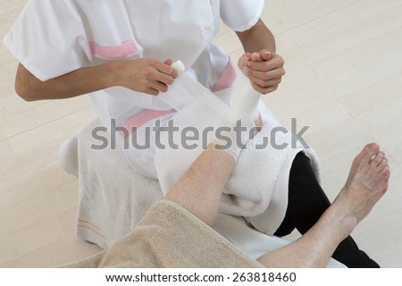 Nurse taking care of senior woman in retirement home bandaging her ankle and foot - stock photo