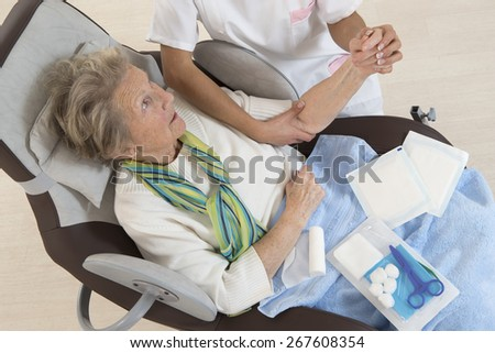 Nurse taking care of senior woman in retirement home bandaging her arm - stock photo
