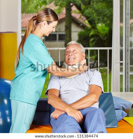 Nurse taking of ruff from senior neck at physiotherapy - stock photo
