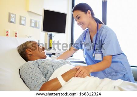 Nurse Talking To Senior Woman In Hospital Room - stock photo