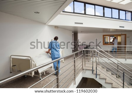 Nurse tending to patient in bed in hospital corridor - stock photo