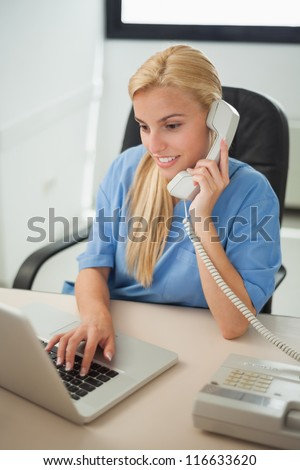 Nurse typing on a laptop while holding a phone in hospital reception - stock photo