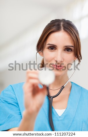 Nurse using a stethoscope in a hallway - stock photo