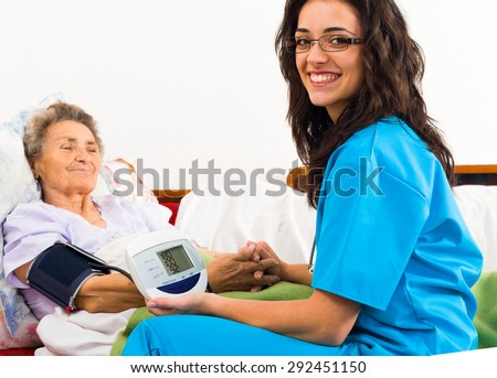Nurse using digital blood pressure for senior patient. - stock photo