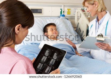 Nurse Using Digital Notepad Whilst Visiting Child Patient - stock photo