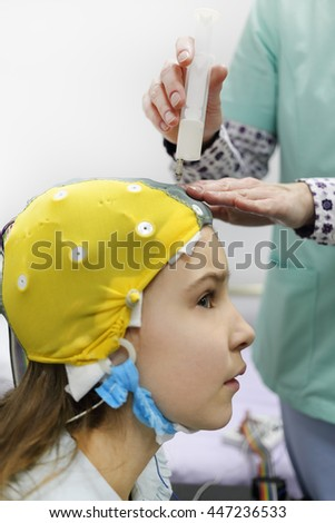 nurse using syringe introduces special gel for electrodes located in cap of electroencephalogram, girl looking to side, focus on syringe
