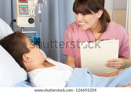 Nurse Visiting Child Patient On Ward - stock photo