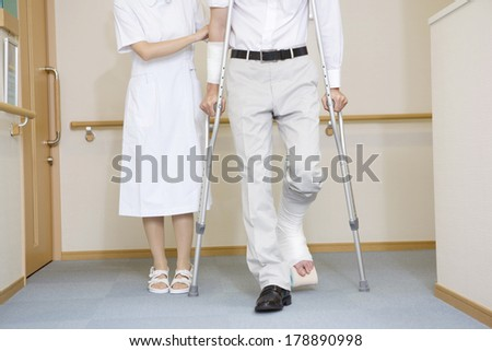 Nurse walking together with a patient with crutches