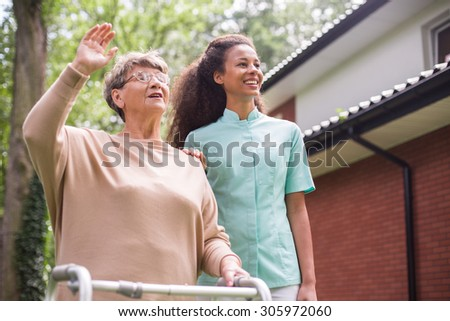 Nurse walking with patient in front of rest home - stock photo