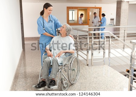 Nurse watching over old women sitting in wheelchair in hallway - stock photo