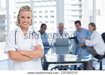 Nurse with arms crossed standing in front of her team - stock photo