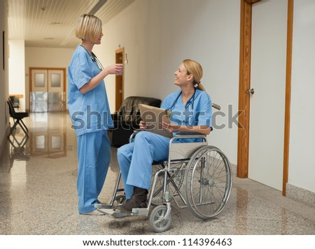 Nurse with drink talking to nurse in wheelchair with folder in hospital corridor
